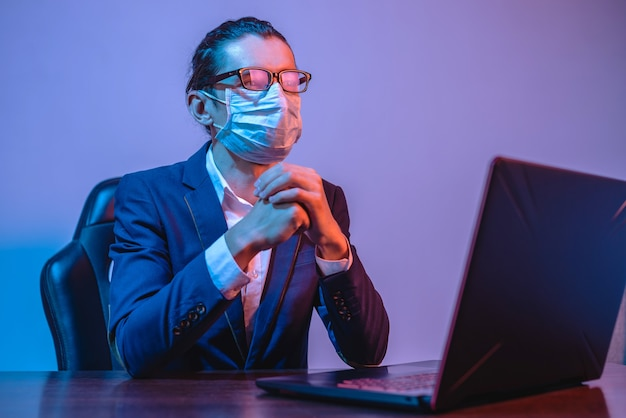 A male businessman in a medical mask works at a laptop in the workplace in dramatic neon light