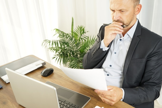 A male businessman reads the text of a document, leaning back in his chair