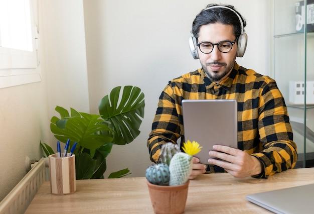装飾されたオフィスに座っている男性実業家は、ヘッドフォンで音楽を聴きながらタブレットを使用しています