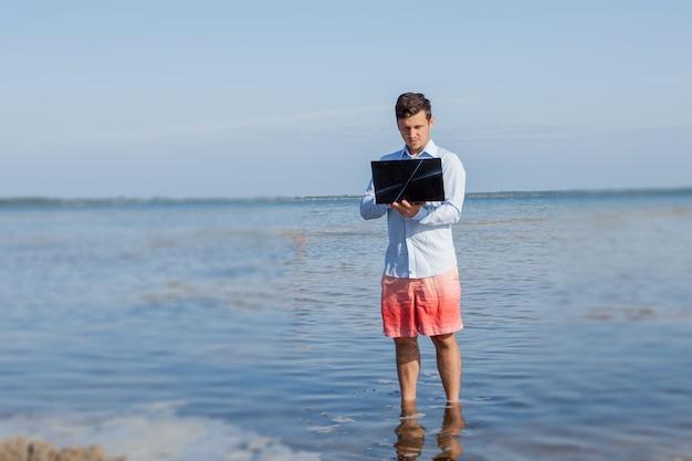 水の中でラップトップを持つ男性のビジネスマン