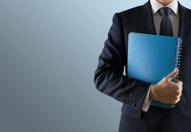 灰色の背景のノートブックレポートを持つ男性実業家