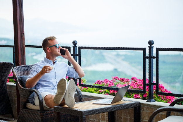 Male businessman working on a laptop on vacation with a beautiful panoramic view. successful manager drinking coffee and talking on the phone with coffee while traveling