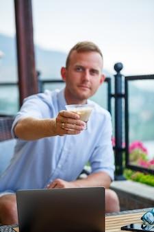 美しいパノラマの景色を望む屋上カフェでノートパソコンに取り組んでいる男性実業家。男のブロガーはコーヒーを飲み、旅行中にコンピューターで作業します
