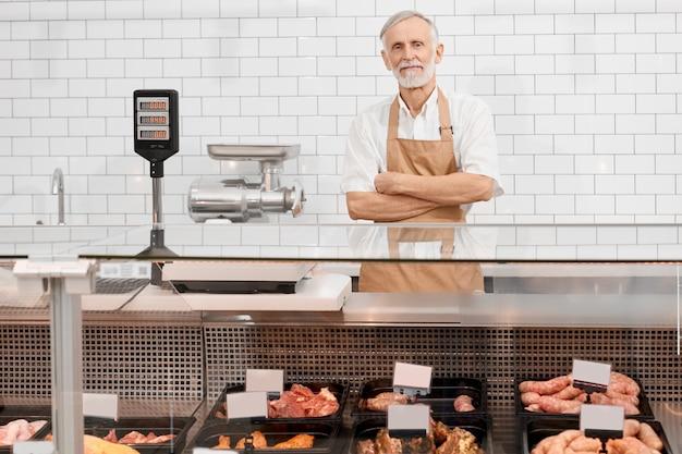 男性の肉屋がカウンターの後ろでポーズします。