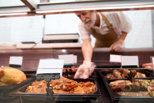 男性の肉屋がカウンターから生の肉を取り出します。