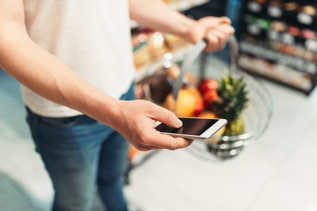 Male buyer hands with basket of fruits and phone