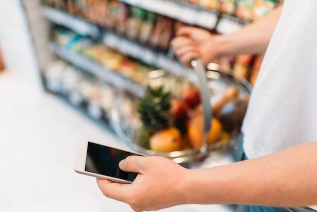 슈퍼마켓에서 과일과 휴대 전화의 바구니와 함께 남성 구매자 손. 식품점이나 식료품 점에있는 남자