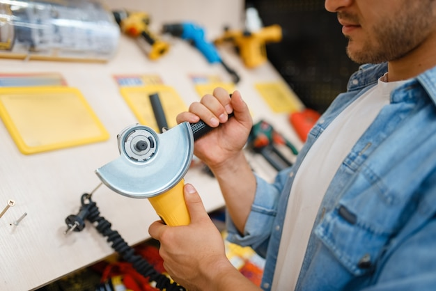 Male buyer holding edging machine in hardware store.