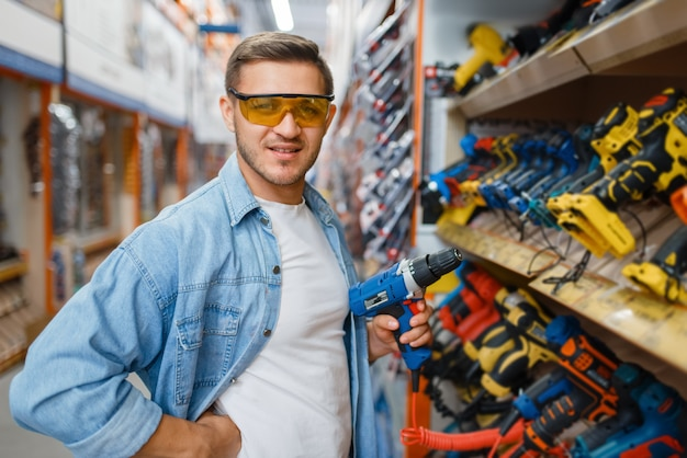 Male buyer holding electric screwdriver in hardware store. customer look at the goods in diy shop, shopping in building supermarket