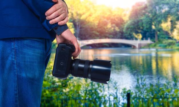 男性のカメラマンがデジタルカメラ、クローズアップ、緑の自然と湖を手に