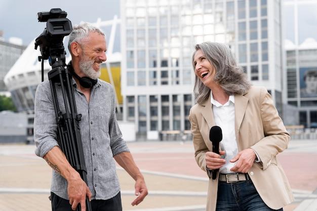 女性ジャーナリストと話している男性カメラマン