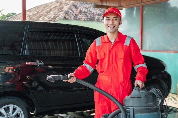자동차 살롱에서 진공 청소기를 들고 빨간색 유니폼 서 입고 남성 자동차 청소기