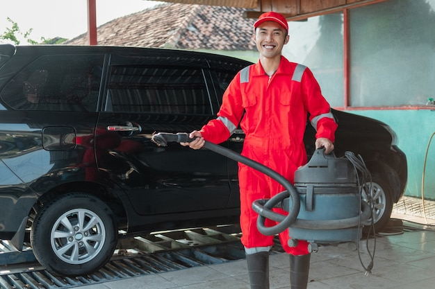 빨간색 유니폼을 입고 남성 자동차 청소기는 자동차 살롱에서 진공 청소기를 들고 웃고 서