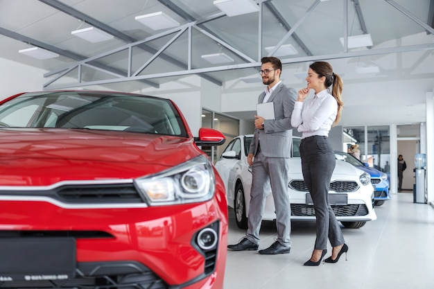 車を買いたいと思っている女性と一緒にカーサロンを歩き回り、車の仕様について話しているスーツを着た男性の車の売り手。