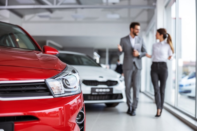 Male car seller in suit walking around car salon with woman who wants to buy a car and talking about specifications of cars
