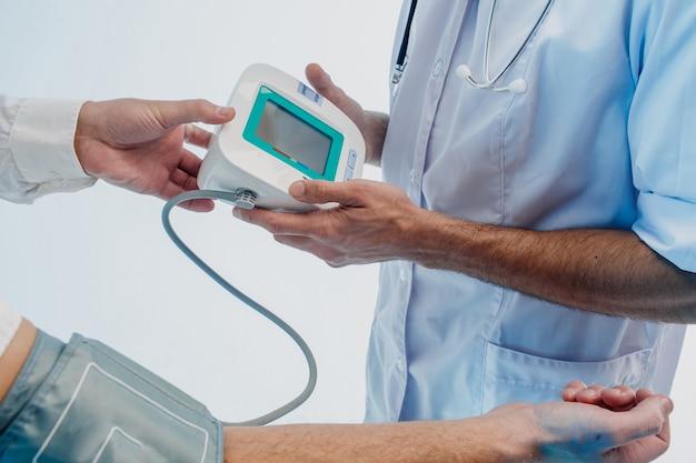 Врач кардиологии мужского пола проверяет пульс пациента с цифровым тонометром. обрезанное изображение лиц. изолированные на сером фоне с бирюзовым светом. студийная съемка. копировать пространство