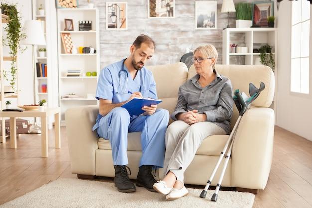 남성 간병인은 요양원에서 노인 여성과 이야기하면서 클립보드에 메모를 합니다.