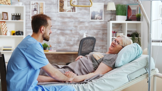 Badante maschio che parla con una vecchia signora malata sdraiata nel letto d'ospedale, prende la mano della donna