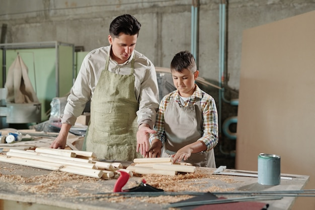 Male carpenter in apron pointing at planks while explaining teenage son how to work with wood in furniture workshop
