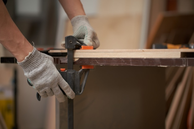 Male carpenter clamps board in vice in workshop