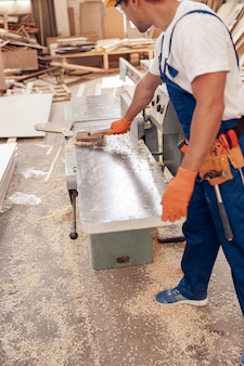 작업장에서 목공 기계를 청소하는 남성 목수