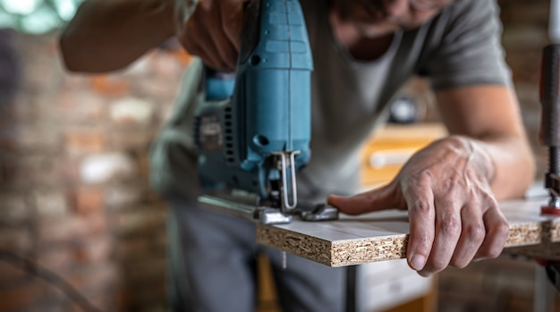 A male carpenter cuts a wood with an electric jigsaw, working with a tree.
