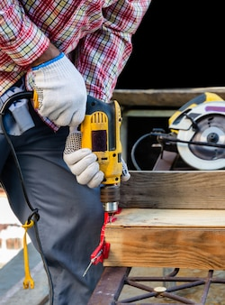 男性の大工は、ねじ込み突合せ継手用の電気コード付きドリルを使用して、木の板に穴を開けます。木工コンセプトのためのツールと機器。