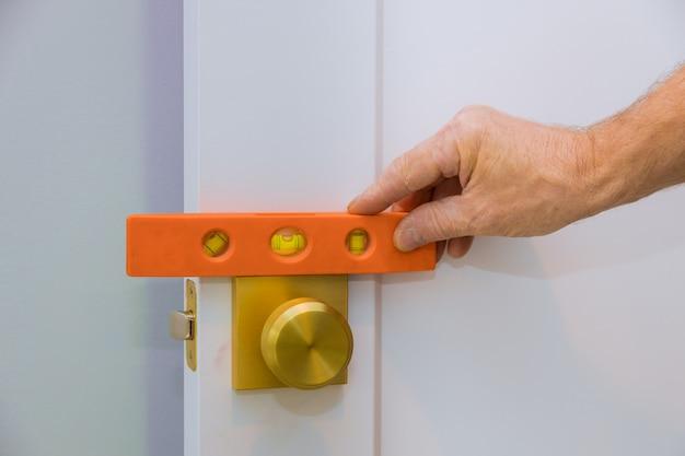 Male carpenter fixing lock in door with home