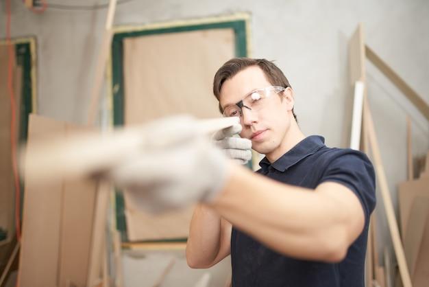 Male carpenter in glasses holds board in workshop