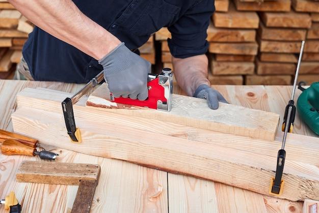 Руки плотника, используя наждачную бумагу на деревянной доске для мебели ручной работы.