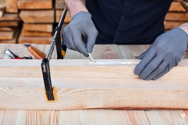 수제 가구 나무 테이블에 나무 접착제와 목재를 사용하는 남성 목수 손.