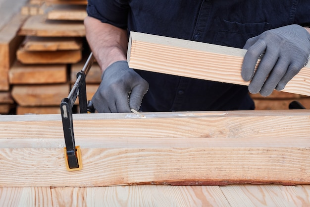 Male carpenter hands using wood glue and timber on a wooden table for handmade furniture.