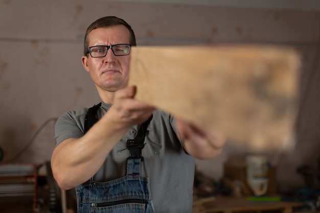 A male carpenter holds a bar of wood at arm's length and evaluates his work.
