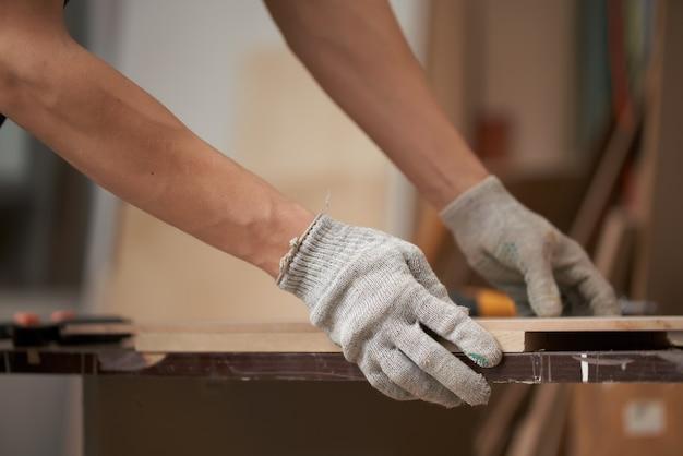 Male carpenter holds board in workshop