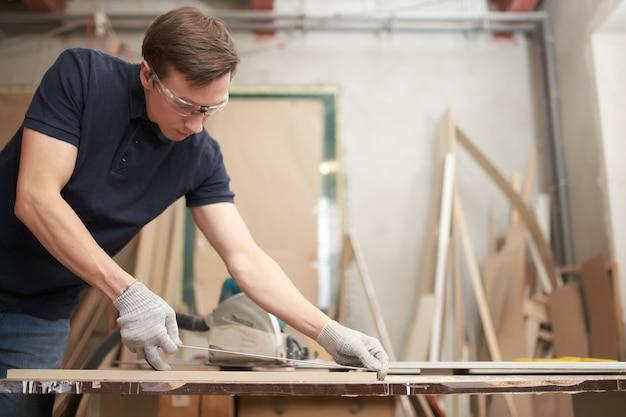 안경을 쓴 남성 목수는 작업장에서 센티미터 테이프로 보드를 측정합니다.