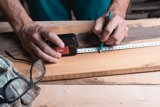 Male carpenter notes with pencil using measuring tape on the board, marks for saw cut
