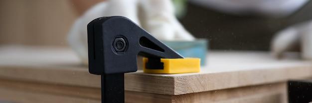 男性大工は木製の板固定万力を磨きます。各種建具・製品の製造。適切な取り付け用ハードウェアの選択と取り付けのスキル。アート家具を作る