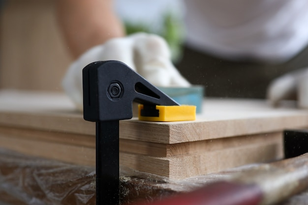 Male carpenter polishes wooden planks fixed vise