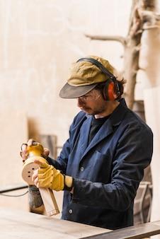 Мужской плотник обрабатывает блок случайным орбитальным шлифовальным станком в мастерской