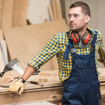 A male carpenter standing in front of workbench looking away