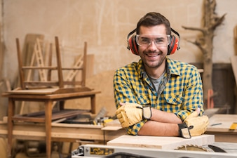 Male carpenter wearing safety glasses and ear defender leaning on table saw in the workshop