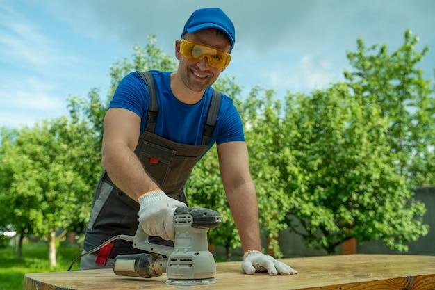 Плотник в защитных очках и перчатках полирует деревянный стол шлифовальным станком в ...