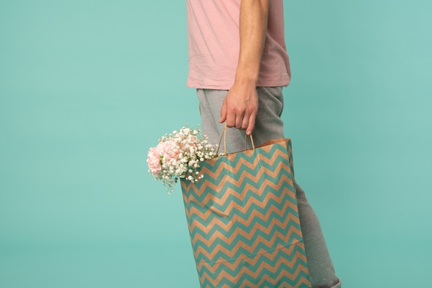 Мужчина несет пакет с цветами на синем фоне с copyspace