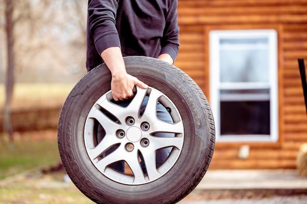 새 자동차 타이어를 들고 남성