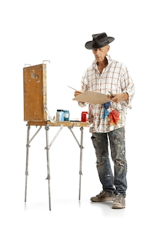男性白人アーティスト、白いスタジオで隔離の仕事で画家