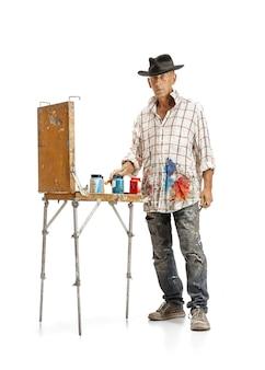 白いスタジオの背景に分離された仕事で男性白人画家
