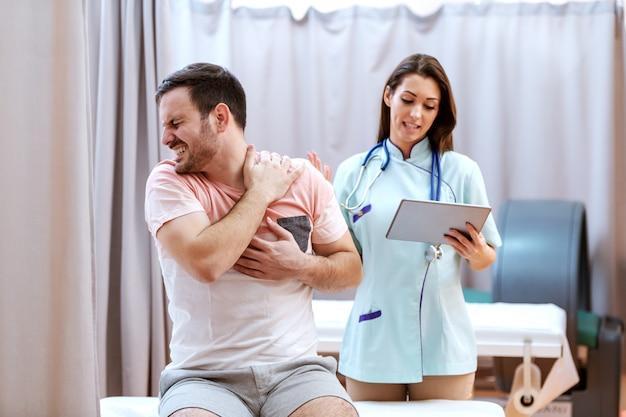Мужской кавказский пациент в боли показывая к доктору причиняя боль место. доктор холдинг планшета и разговаривать с пациентом.