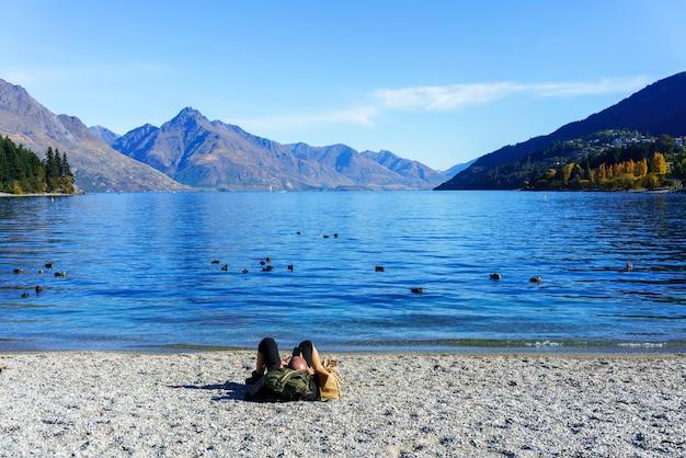 スマートフォンを使用して、ニュージーランドの南島、クイーンズタウン、ワカティプ湖のビーチでリラックスした男性の白人