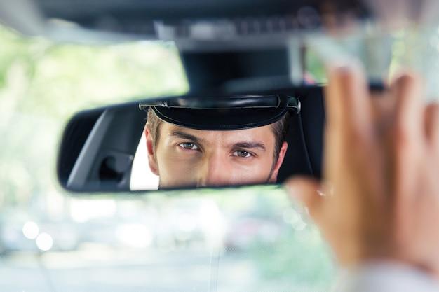 차에 앉아 거울에 자신의 반사를보고 남성 운전사