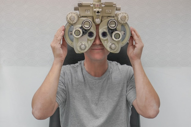 Мужчина проверяет свое зрение на машине, проверяющей зрение пациента в офтальмологической клинике или магазине оптики.